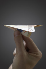 Person holding paper airplane made of 50 euro note, close-up of hand