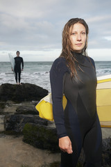 Female surfer carrying surfboard standing on beach, another surfer standing in background, portrait