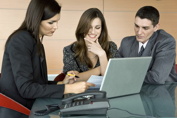 Professional woman looking over paper with couple