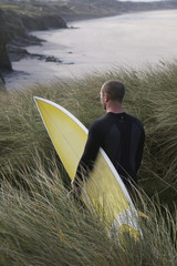 Man carrying surfboard down hill torwards sea, back view
