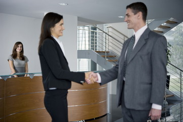 Businessman and woman shaking hands in reception