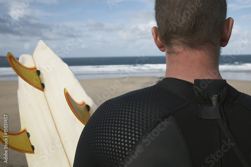 Man holding surfboard on beach looking at sea, back view, close up