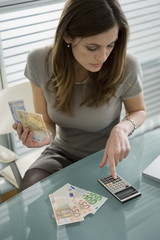 Professional woman adding up euro bills with calculator