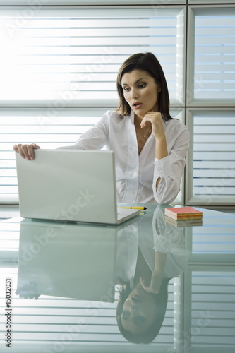 Professional woman looking at laptop in surprise