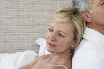Middle-aged couple sitting back to back in bedroom, close-up