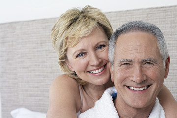 Portrait of middle-aged couple in bedroom, close-up