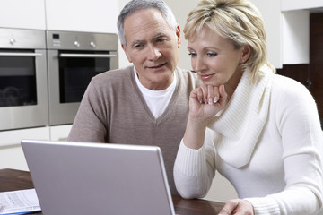 Middle-aged couple counting bills using laptop in kitchen