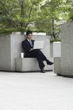 China, Hong Kong, business man sitting on stone bench using laptop