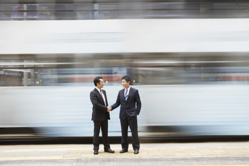 China, Hong Kong, two business man shaking hands, standing on street crossing, long exposure