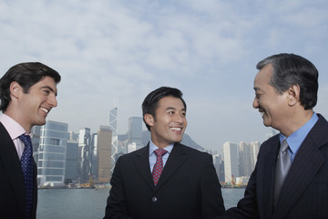 Three business men smiling, office buildings in background