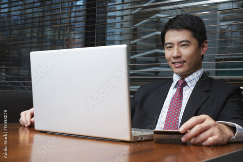 Business man using laptop in cafe