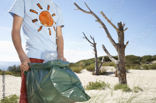 Boy 10-12 holding plastic bag, on sand dune, mid section