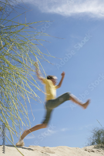Boy 10-12 jumping on sand dune