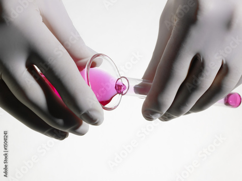 Person wearing rubber gloves pouring pink liquid into vial, close up, studio shot