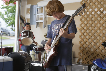 Two boys 10-12 playing drums and guitar in garage