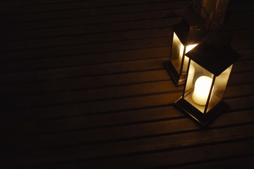 Two illuminated lanterns on deck at night