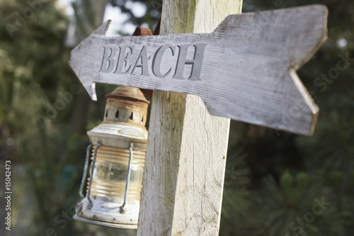 Wooden post with lantern and arrow reading 'beach'