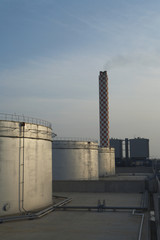 Fuel oil storage tanks with power station and smokestack in background