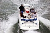Small White Motor Boat With Five People Aboard poster