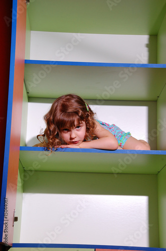 pretty little girl hiding on the shelf in the colorful bookcase
