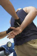 Police man putting handcuffs on criminal