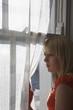 Teenage girl 16-17 looking through window