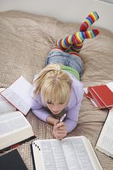 Teenage girl 16-17 doing homework lying on bed