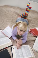 Portrait of teenage girl 16-17 doing homework on bed