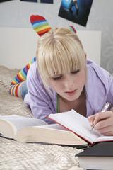 Teenage girl 16-17 doing homework on bed