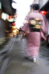 Japan, Kyoto, Pontocho-dori, Woman wearing kimono walking on narrow street, motion blur