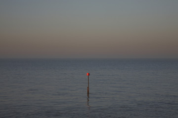 Beacon in ocean at dusk