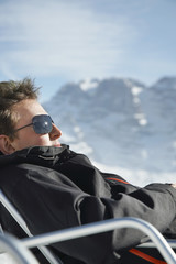 Man in winter coat and sunglasses sitting in arm chair by mountains