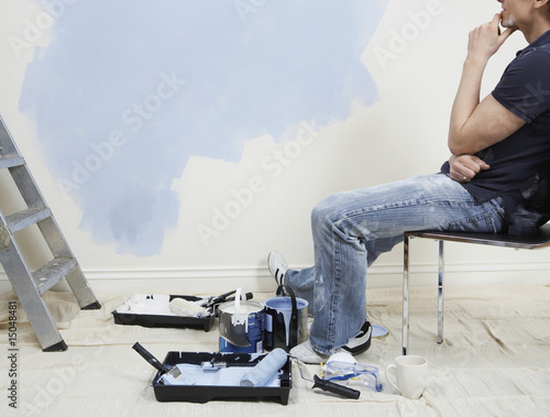 Man resting while painting wall, low section
