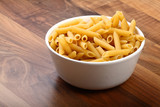 Dry penne rigate in white ceramic bowl on wooden floor