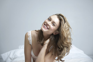 Young woman wearing bra, smiling on bed, portrait