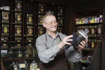 Tea Shop Owner Dusting Jar of Tea