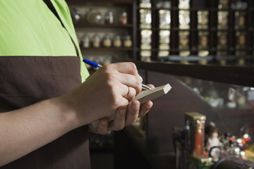 Salesperson Writing Order in Tea Shop