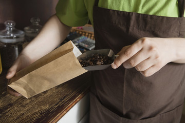 Salesperson Scooping Coffee Beans Into Bag