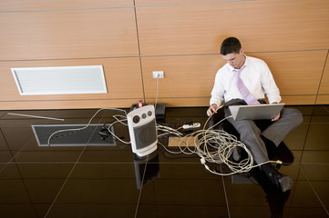 Office worker on floor with wires and laptop