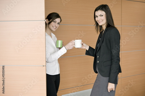 Businesswoman bringing coffee to another businesswoman
