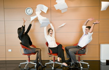 Office workers throwing documents up in the air