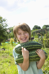 Boy holding marrow in garden, portrait