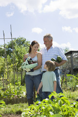 Family with boy holding vegetables in garden