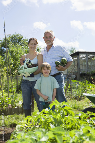 Family with boy holding vegetables in garden, portrait