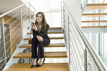 Businesswoman looking at cell phone on office staircase