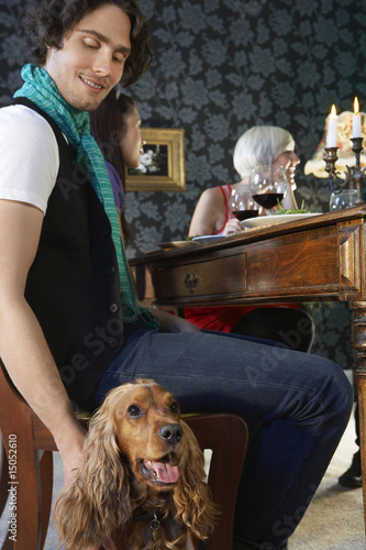 Man petting dog sitting near dining table