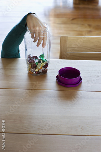 Hand of child taking candies from jar