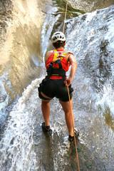 Woman climbing a waterfall