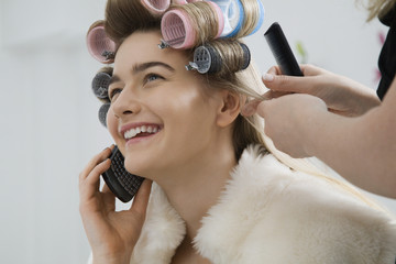Model on Cell Phone While Having Hair Curled