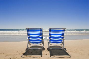 Zwei Sonnenliegen am Strand